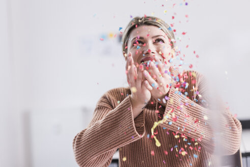 Happy young woman throwing confetti in the air - UUF12860