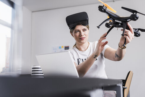 Young woman with laptop and VR glasses at desk holding drone - UUF12863