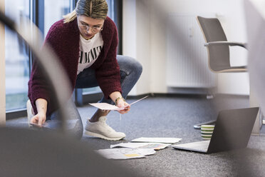 Young woman with laptop and documents working on the floor in office - UUF12866