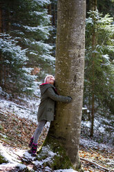 Girl hugging tree in forest in winter - LBF01803