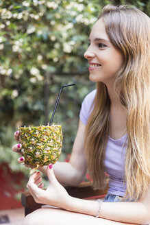 Smiling young woman drinking a cocktail in pineapple outdoors - LFEF00061
