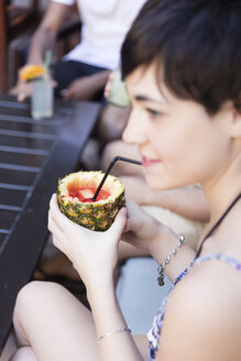 Smiling young woman with friends outdoors drinking a cocktail in pineapple - LFEF00067