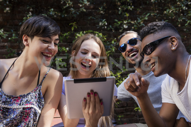 Happy friends sharing tablet outdoors - LFEF00070