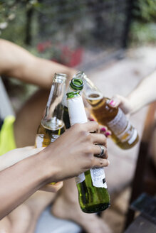 Close-up of friends toasting with beer bottles outside - LFEF00076