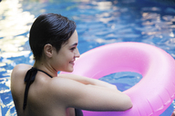 Smiling young woman with inflatable tube in swimming Pool - LFEF00103