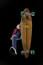 Happy young woman driving longboard seen from below - STSF01469