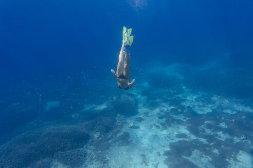 Woman with fins and snorkel diving under water - KNTF01024