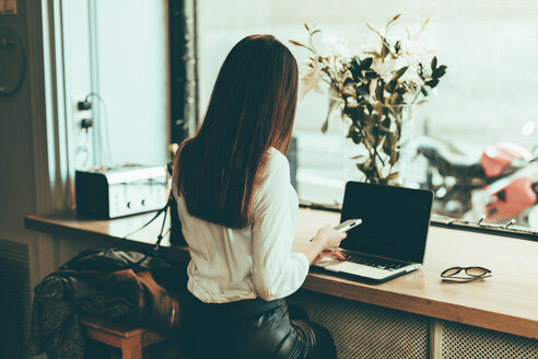 Back view of businesswoman using laptop and cell phone in a coffee shop - OCAF00154