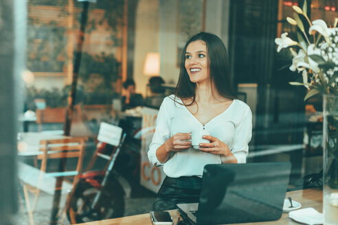 Portrait of laughing young woman waiting in a coffee shop - OCAF00157