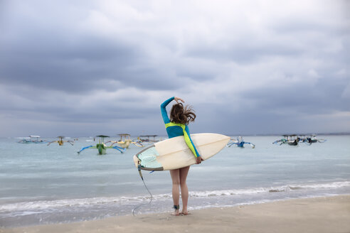 Indonesia, Bali, young woman with surf board - KNTF01037
