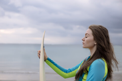 Indonesia, Bali, young woman with surf board - KNTF01040