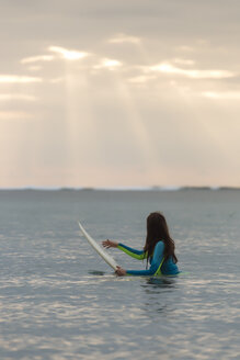 Indonesia, Bali, young woman with surf board in water - KNTF01043