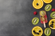 Berries, fruit slices and kiwi berry popsicle on grey background - SKCF00338