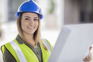 Portrait of smiling woman wearing hard hat and reflective jacket holding plan - ZEF15056