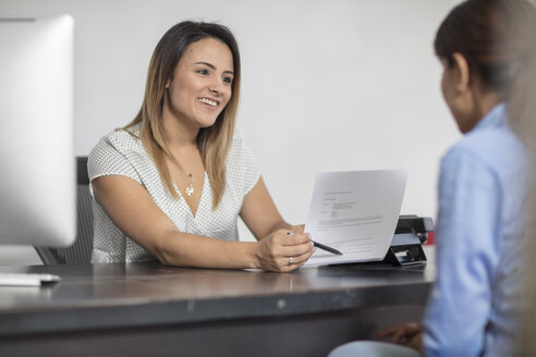Smiling woman showing contract to client at desk - ZEF15065