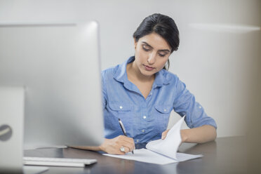 Businesswoman taking notes at desk in office - ZEF15068