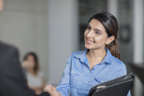 Smiling woman in office shaking hands - ZEF15074