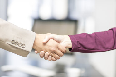 Close-up of businessman and businesswoman shaking hands - ZEF15085