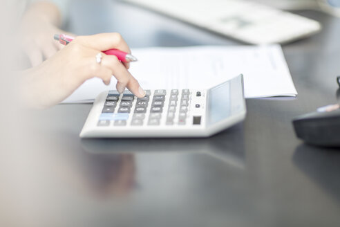Woman at desk in office using calculator - ZEF15088