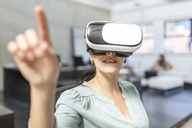Woman wearing VR glasses in office - ZEF15091