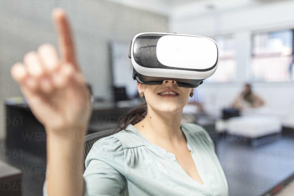 Woman wearing VR glasses in office - ZEF15091 - zerocreatives/Westend61