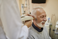 ENT physician examining ear of a senior man - ZEDF01236