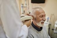 ENT physician examining ear of a senior man - ZEDF01236