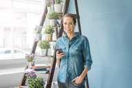 Beautiful woman in her home, decorated with plants, holding smartphone, smiling - MOEF00860