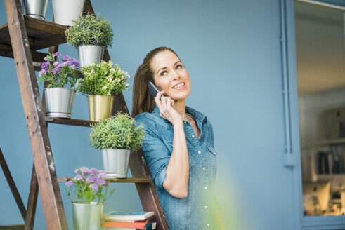 Beautiful woman in her home, decorated with plants, talking on the phone - MOEF00863