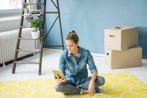 Woman sitting on floor of her new apartment, using digital tablet - MOEF00866