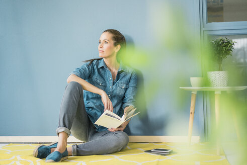 Woman relaxing in her home with potted plants, reading a book - MOEF00869