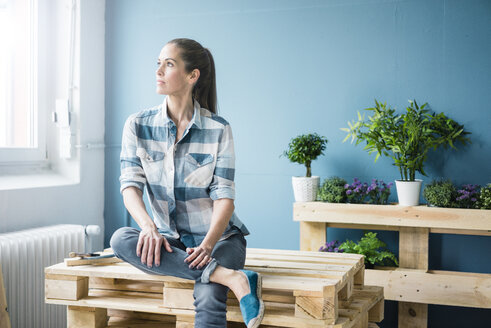 Beautiful woman planning to refurbish her home with pallets - MOEF00875
