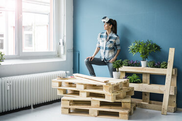 Woman using VR glasses, renovating her new home - MOEF00878