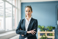 Businesswoman standing at home, with arms crossed - MOEF00881