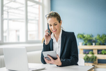 Businesswoman sitting at desk, talking on the phone, looking at digital tablet - MOEF00884