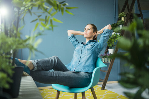 Beautiful woman sitting in her home, decorated with plants, daydreaming - MOEF00887