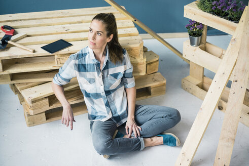 Beautiful woman planning to refurbish her home with pallets - MOEF00893