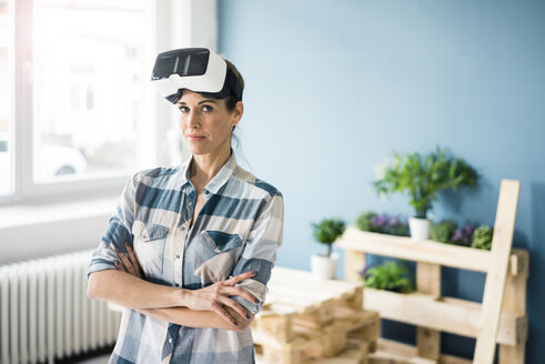 Woman using VR glasses, renovating her new home - MOEF00896