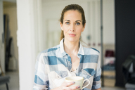 Portrait of a beautiful woman, drinking coffee at home - MOEF00899