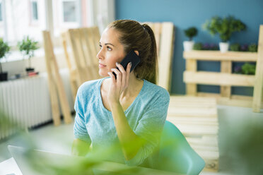 Woman talking on the phone in her new home - MOEF00908