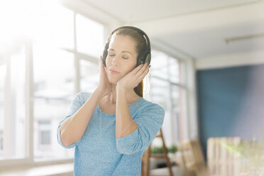 Portrait of a beautiful woman, listening music with headphones - MOEF00911