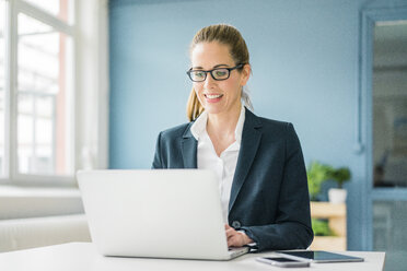 Businesswoman using laptop at home - MOEF00917