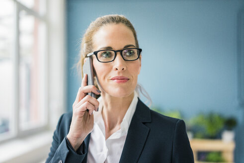 Successful businesswoman standing at home, talking on the phone - MOEF00920