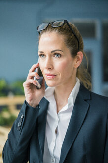 Successful businesswoman standing at home, talking on the phone - MOEF00923