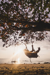 Thailand, Phi Phi Islands, Ko Phi Phi, man on tree swing on the beach in backlight - KKAF00893