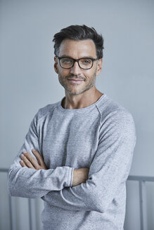 Portrait of smiling man with stubble wearing grey sweatshirt and glasses - PNEF00547
