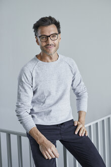 Portrait of smiling man with stubble wearing grey sweatshirt and glasses - PNEF00550