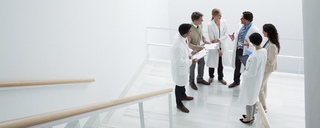 Business people and doctors meeting on landing of stairs - CAIF00014
