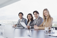 Portrait of smiling business people sitting in a row in conference room - CAIF00026