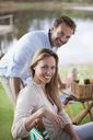 Portrait of smiling couple enjoying picnic at lakeside - CAIF00035